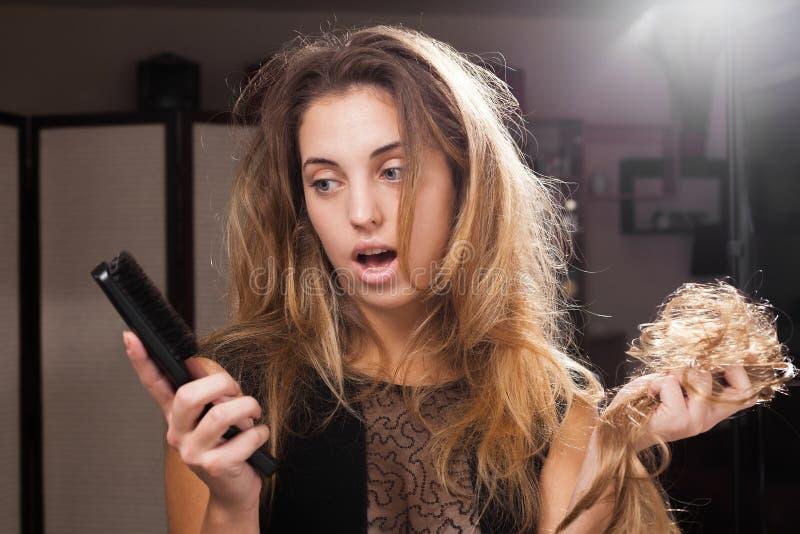_déconcerter joli fille découvrir perte des cheveux sur un brosse à cheveux image stock