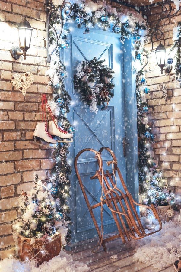 Décoré pour maison de Noël, porte bleue, traîneau et patins à glace photo stock