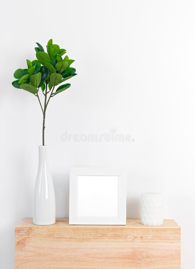 Décor élégant avec le cadre de tableau, les feuilles de ficus et la bougie blancs photo libre de droits