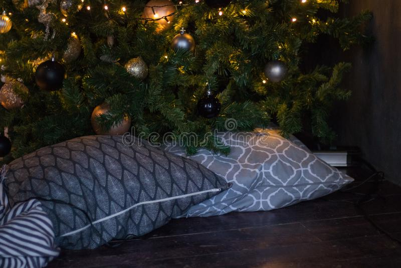 Décor d'hiver : Arbre de Noël, guirlande, boules, cadeaux et plaid rayé confortable avec des oreillers Orientation choisie photos libres de droits