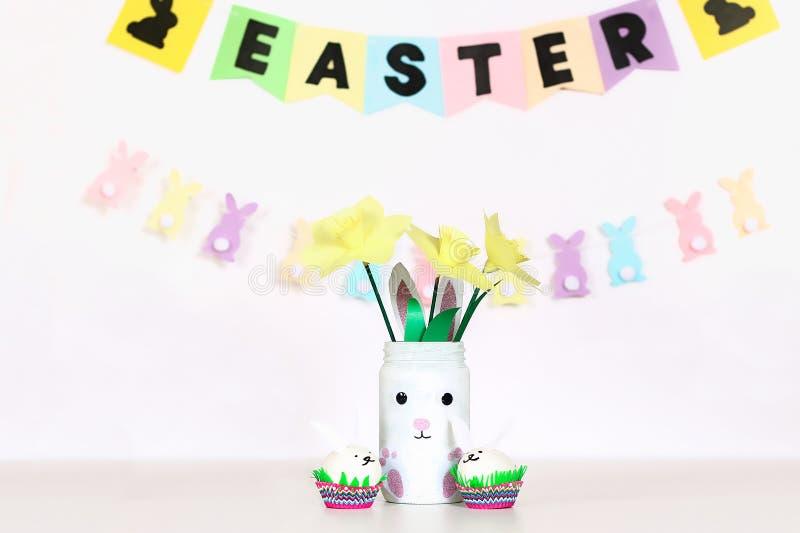 Décor de Diy pour Pâques Guirlandes de papier, lapin de vase, jonquilles, lapins d'oeufs, panier avec les oeufs peints photographie stock libre de droits