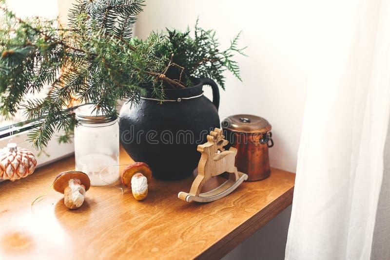 Décor de noël élégant sur un rebord de bois Branches de pins à bauble d'époque, cerf de bois, lanterne, jouets de champignons sur image stock