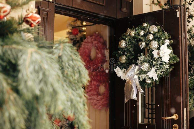 Décor de rue de Noël. Une élégante couronne de noël avec des ornements d'argent à la porte du magasin de devant au marché d image libre de droits