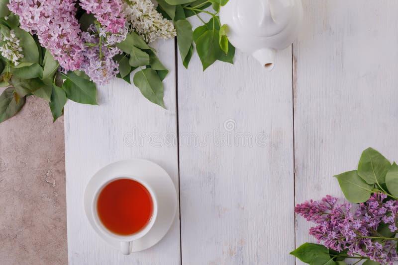 Décor de service à thé et de fleur sur un fond des conseils en bois blanc-peints Fond de cru avec des fleurs lilas et un endroit images stock