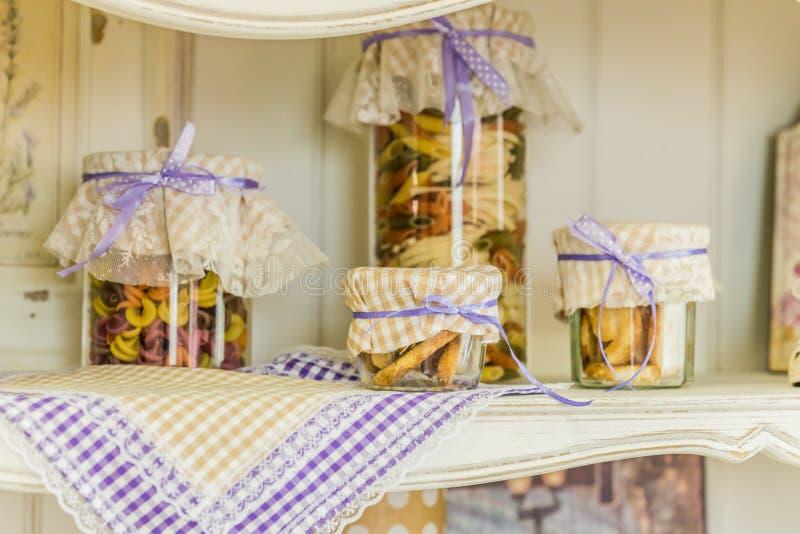 Décor provençal, ustensiles de cuisine sur une étagère suspendue, pâtes fermées dans des jarres image libre de droits
