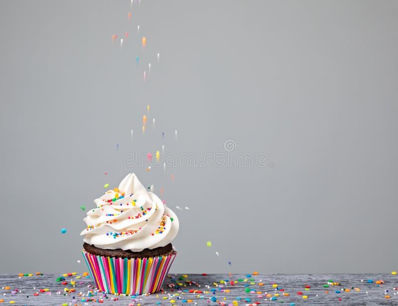 Décorant un petit gâteau avec arrose photographie stock