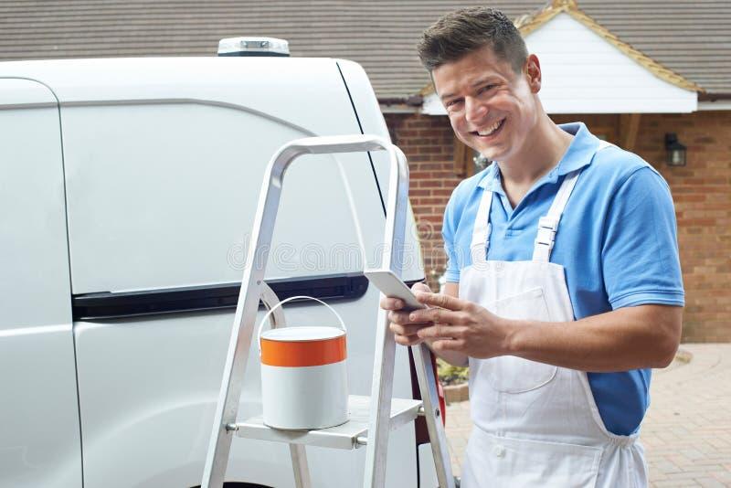 Décorateur employant la maison domestique d'extérieur debout de téléphone portable photo libre de droits