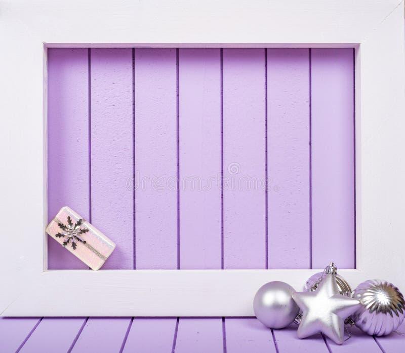 Décoration blanche de cadre en bois et de Noël au-dessus d'un fond pourpre images stock