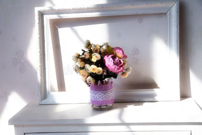 Décoration, cadre de tableau et fleurs à la maison sur la table de chevet photo stock
