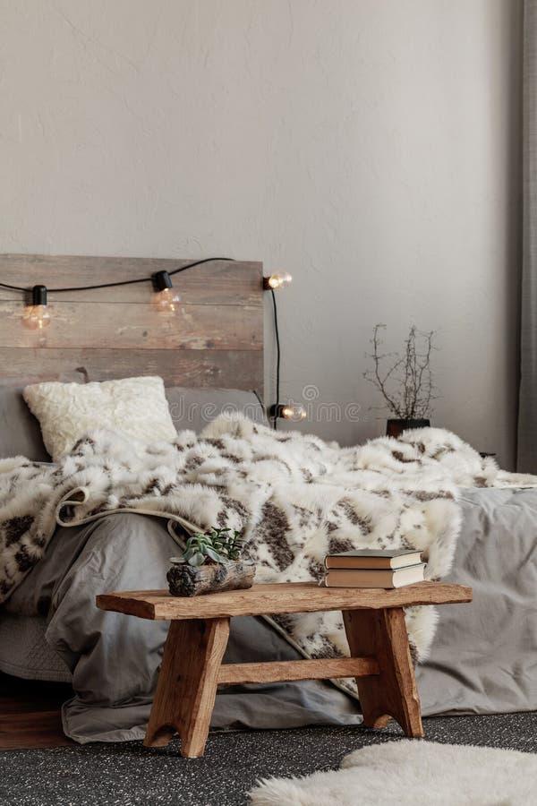 Décoration chaleureuse de la chambre avec lit king size avec tête de lit en bois clair, couverture furieuse et table de nuit noir photo stock