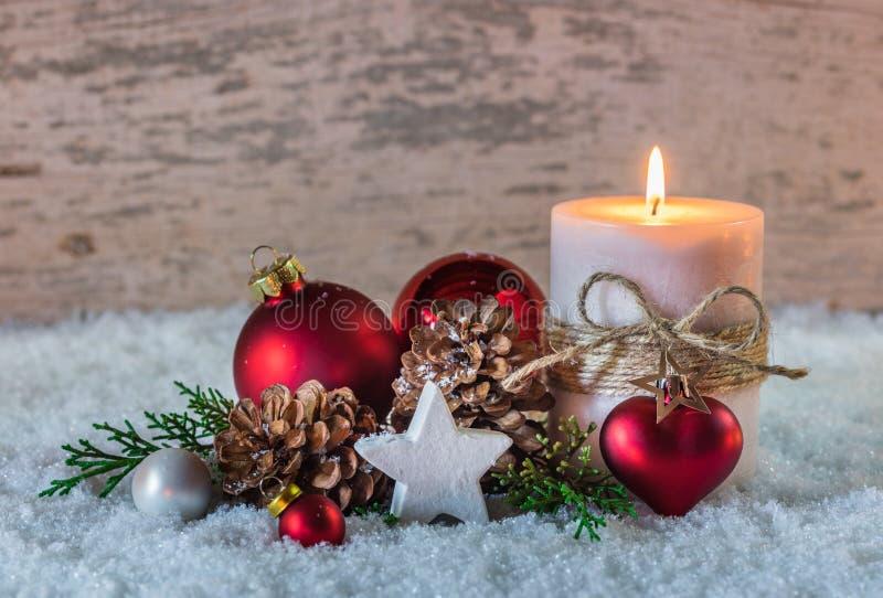 Décoration d'hiver de célébration de vacances de Noël avec la bougie brûlante avec le coeur rouge sur la neige et le fond en bois image stock