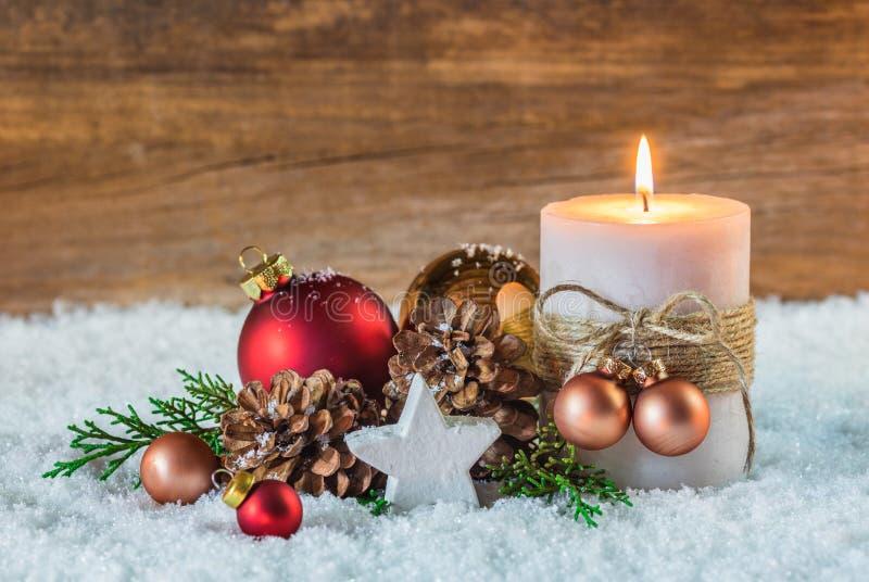 Décoration d'hiver de célébration de vacances de Noël avec la bougie brûlante sur la neige et le fond en bois photographie stock