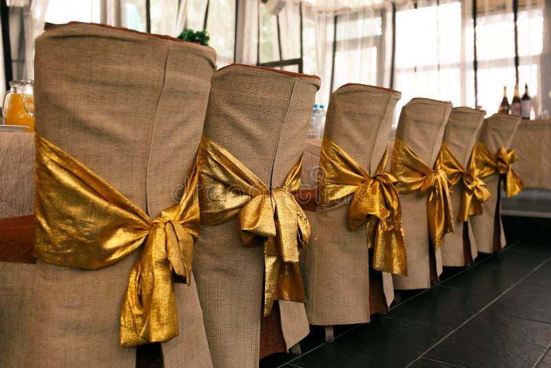 Décoration de chaise de mariage Les couvertures de beige et les cintrages d'or de la chaise soutient photos stock