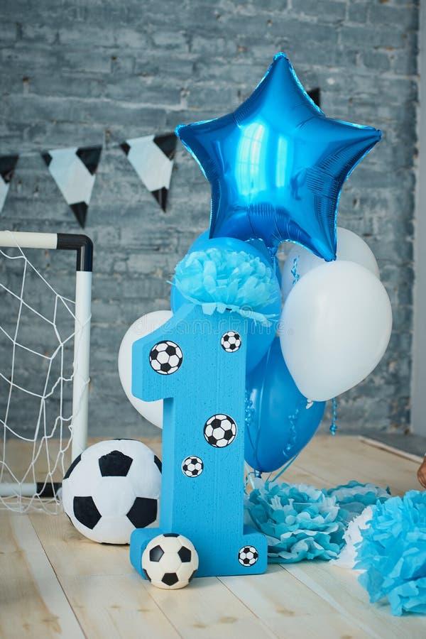 Décoration de fête de fond pour l'anniversaire avec le gâteau, lettres indiquant un et ballons bleus dans le studio, anniversaire photographie stock