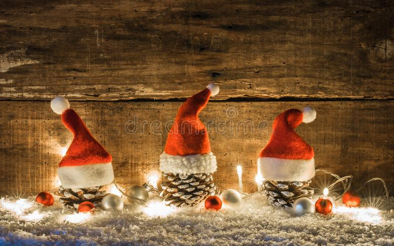 Décoration de Noël avec des cônes de pin décorés des chapeaux rouges du père noël au-dessus de la neige avec la lumière et les or photographie stock
