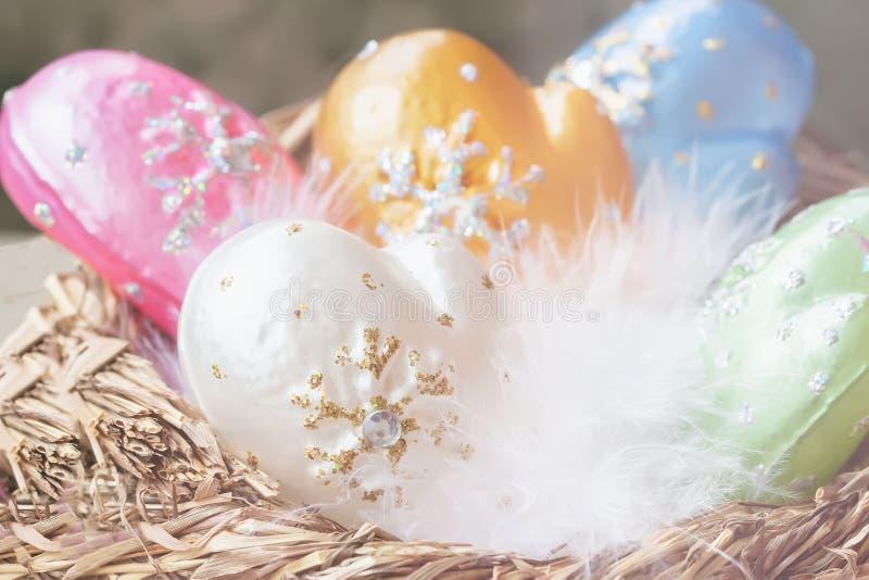 Décoration de Noël des mitaines décoratives colorées de celluloïde avec le duvet blanc d'oiseau dans l'élément de nid de Noël image stock