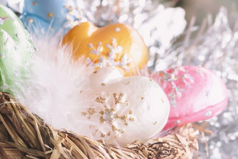 Décoration de Noël des mitaines décoratives colorées de celluloïde avec le duvet blanc d'oiseau dans l'élément de nid de Noël image libre de droits
