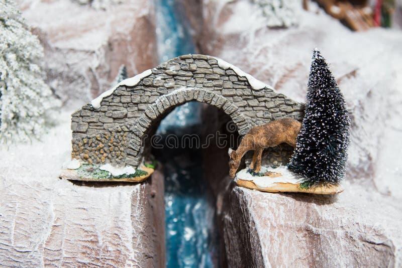 Décoration de décoration de Noël la grande des cerfs communs de gypse boit l'eau de la course de rivière en hiver sur la neige bl photo libre de droits