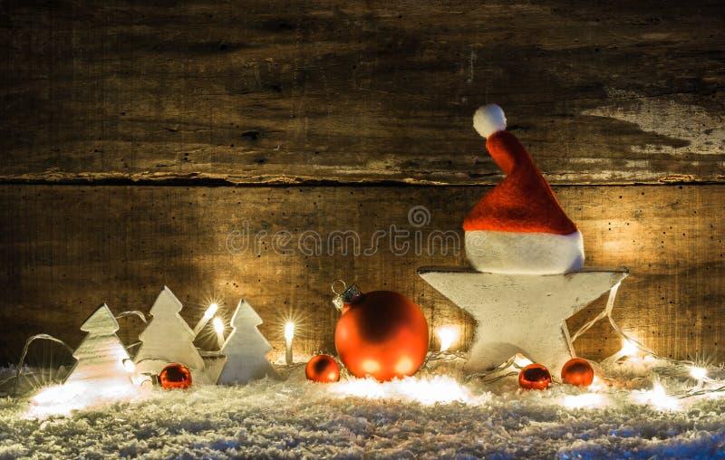 Décoration de scène de Noël avec l'étoile blanche, le chapeau du père noël, les boules rouges, les arbres de Noël et les lumières image libre de droits