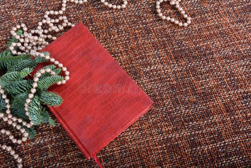 Décoration de vacances avec perles, perles, branches de sapin et livre rouge photo libre de droits