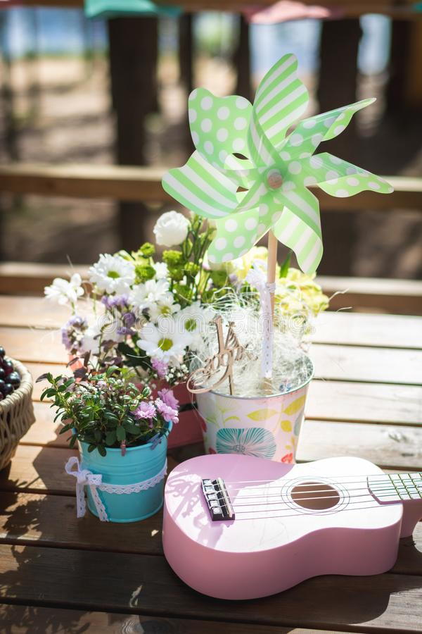 Décoration extérieure de fête d'anniversaire d'été sur une table en bois Soleil vert, fleurs et ukulélé rose image libre de droits