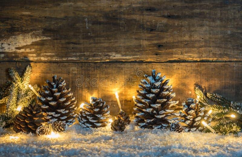 Décoration naturelle de fond de Noël avec des cônes, des branches vertes et la lumière au-dessus de la neige image stock