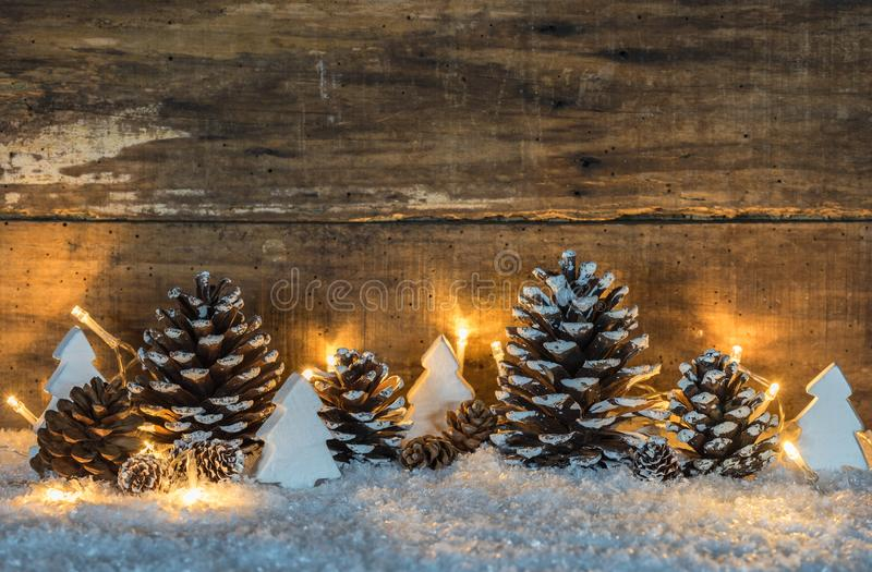 Décoration naturelle de Noël avec des cônes, des lumières et des arbres de Noël au-dessus de neige photo libre de droits