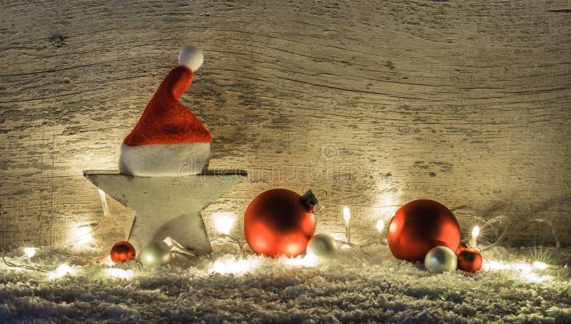 Décoration rouge de Noël blanc, étoile avec le chapeau de Santa, boules et lumière sur la neige image libre de droits