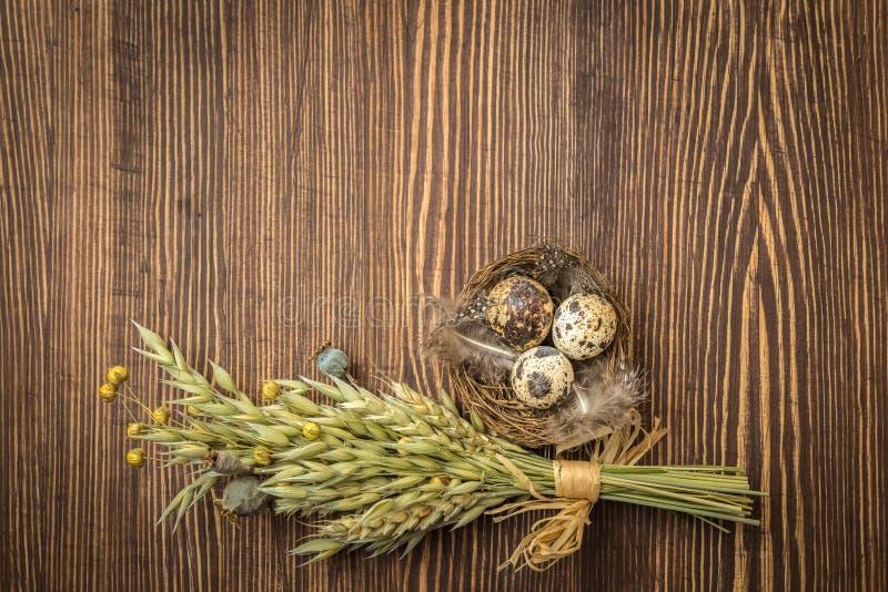 Décoration rustique de Pâques de style - nid avec les oeufs et le bouquet des herbes sèches sur le fond en bois de cru photos libres de droits