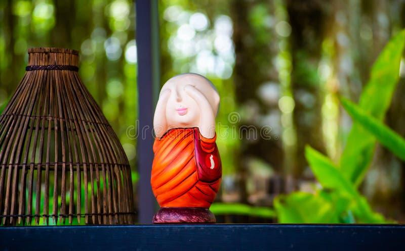 Décoration soignée, petite poupée de moine et panier en bois dans le café local de Wat Rai Cheon Ta Wan, Chiangrai, Thaïlande images libres de droits