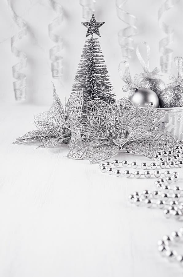 Décorations argentées modernes de Noël sur le plâtre blanc, fond en bois image stock