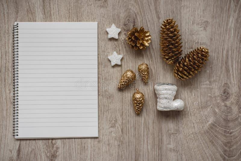 Décorations de Noël, botte blanche de ` s de Santa, cônes de sapin d'or, flocons de neige et un carnet vide ouvert, fond en bois photographie stock libre de droits