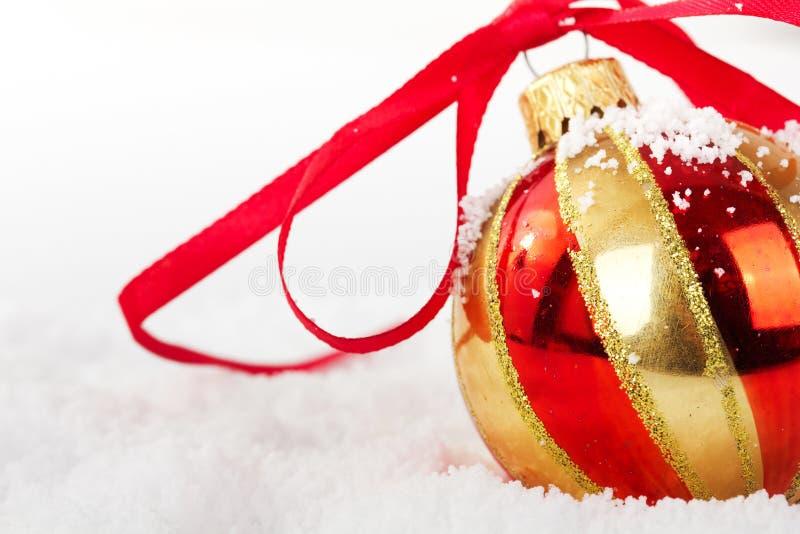 Décorations de Noël d'or dans la neige blanche pour le fond photo stock