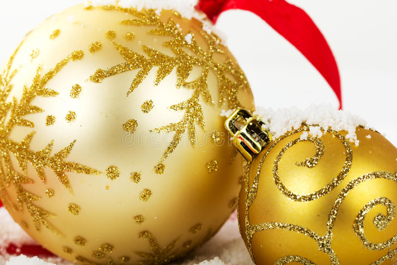 Décorations de Noël d'or dans la neige blanche pour le fond photographie stock