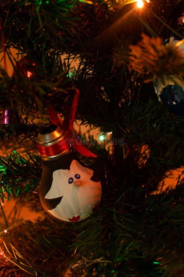 Décorations de Noël Les jouets de nouvelle année : pingouin sur un arbre de nouvelle année Joyeux Noël et bonne année images libres de droits