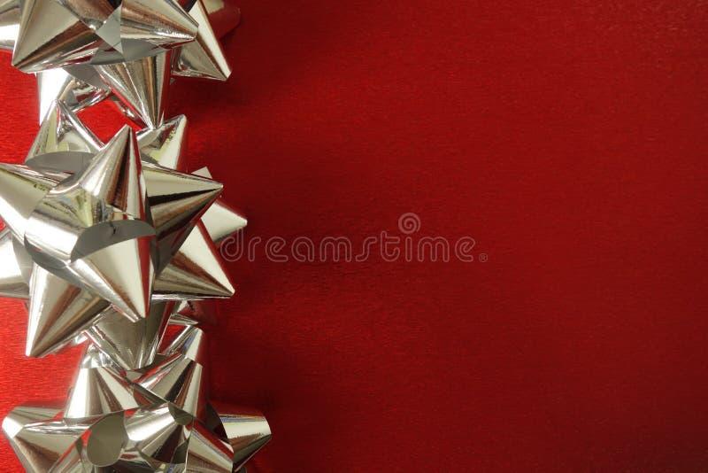 Décorations en forme d'étoile argentées sur le fond de fête rouge image stock