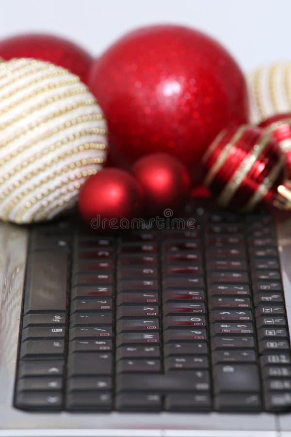 Décorations et ordinateur portable colorés de boules de Noël photographie stock
