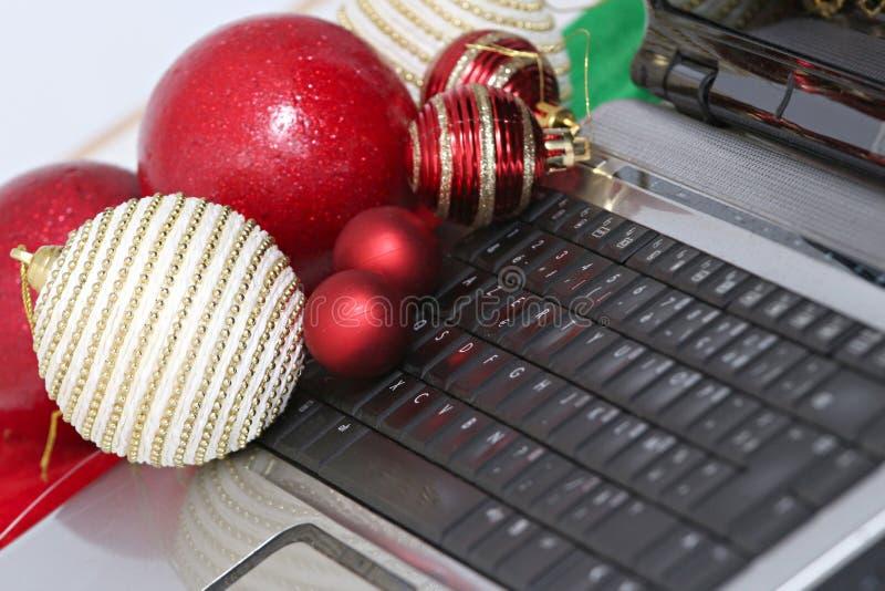 Décorations et ordinateur portable colorés de boules de Noël photos libres de droits