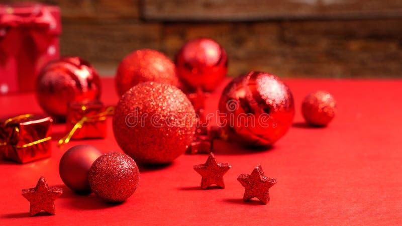 Décorations modernes brillantes de Noël se trouvant sur une table rouge devant un vieux mur en bois photos libres de droits