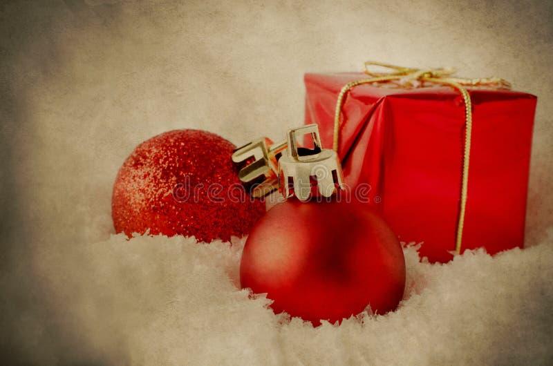 Décorations rouges de Noël dans la neige - grunge de vintage photographie stock