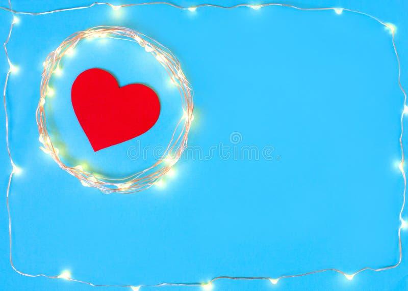 Décorations sous forme de coeur sur un fond bleu avec une guirlande photo libre de droits