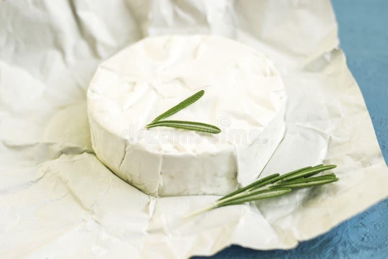 Découpé en tranches autour des laitages crémeux de lait traditionnel de fromage de camembert avec le romarin photos stock