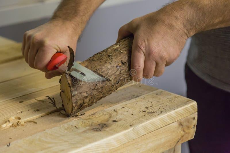 Découpage d'un morceau de bois avec un couteau pointu photo stock