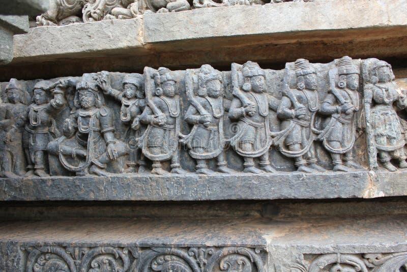 Découpage de mur de temple de Hoysaleswara des démons marchant pour la guerre de combat images stock