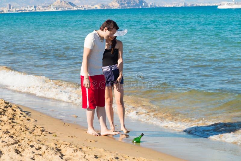 Découverte d'une bouteille sur la côte photo stock