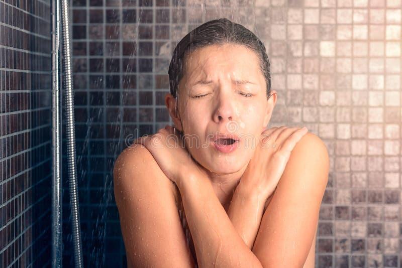 Découvrez la femme réagissant tout en prenant la douche froide photos libres de droits