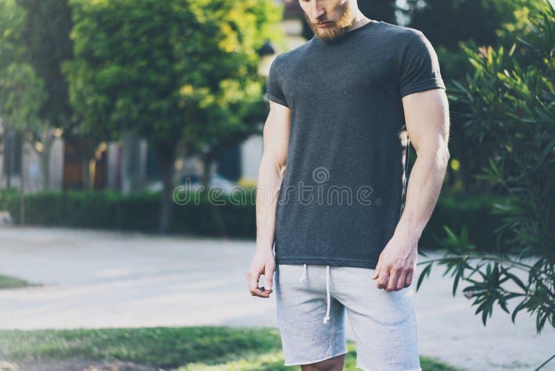 Décrivez l'homme musculaire barbu utiliser le T-shirt vide noir dans l'heure d'été Jardin vert de ville Temps de détente après du photographie stock