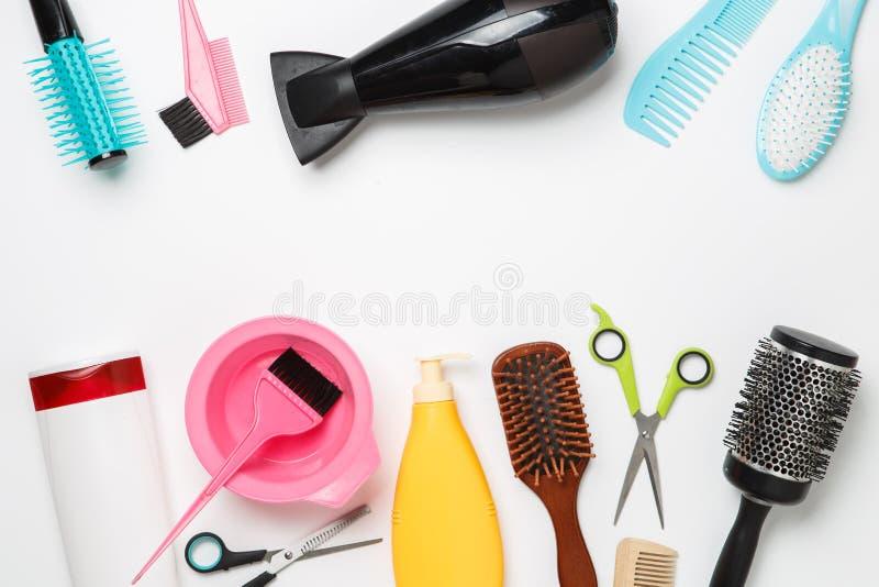 Décrivez les accessoires coiffeur, sèche-cheveux, peigne, bandes de cheveux d'isolement sur le fond blanc image stock