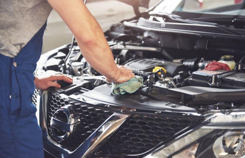 Décrivez montrer le travailleur musculaire de service de voiture réparant le véhicule image stock