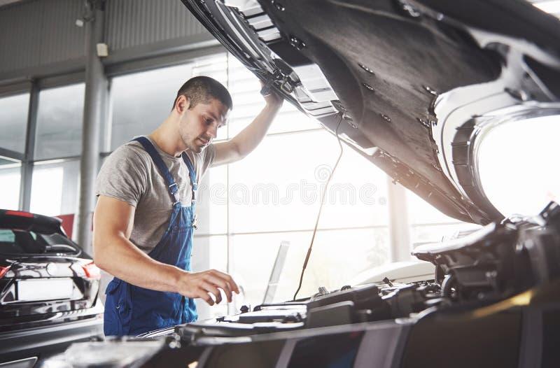 Décrivez montrer le travailleur musculaire de service de voiture réparant le véhicule photos libres de droits
